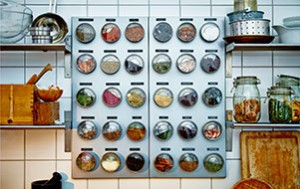 On a white tiled kitchen wall hangs a silver colored magnetic board with stainless cointainers with clear lids on it__20152_idsm01a_01_thumb_PH122242